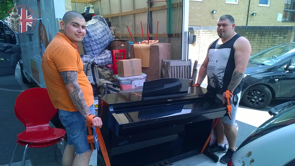 Movers lifting a piano